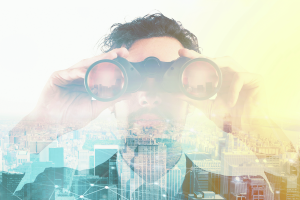 Businessman looks at the city from the roof with binoculars Bild: alphaspirit/Fotolia