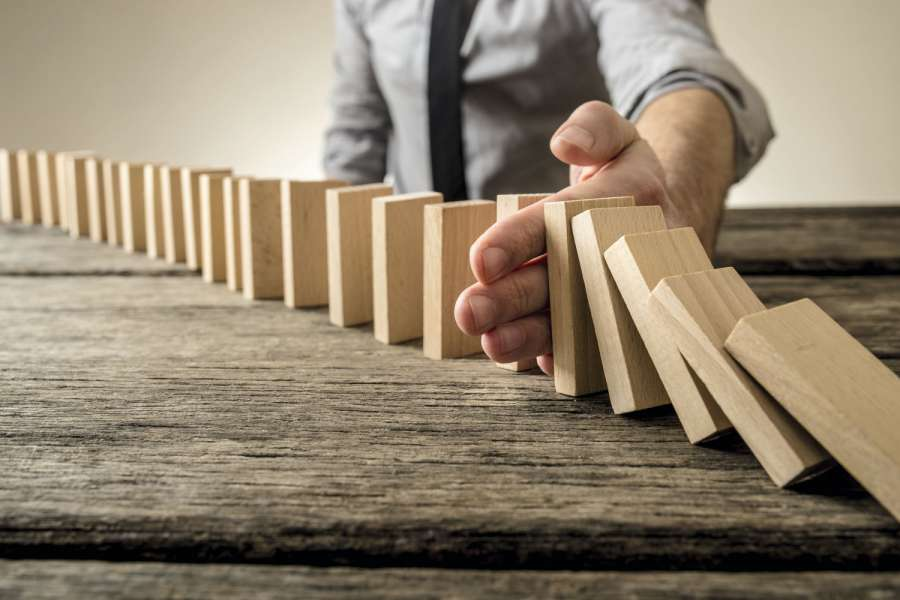 Man stopping domino effect on wooden table. Business success concept. Copy space. Bild: Gajus/AdobeStock