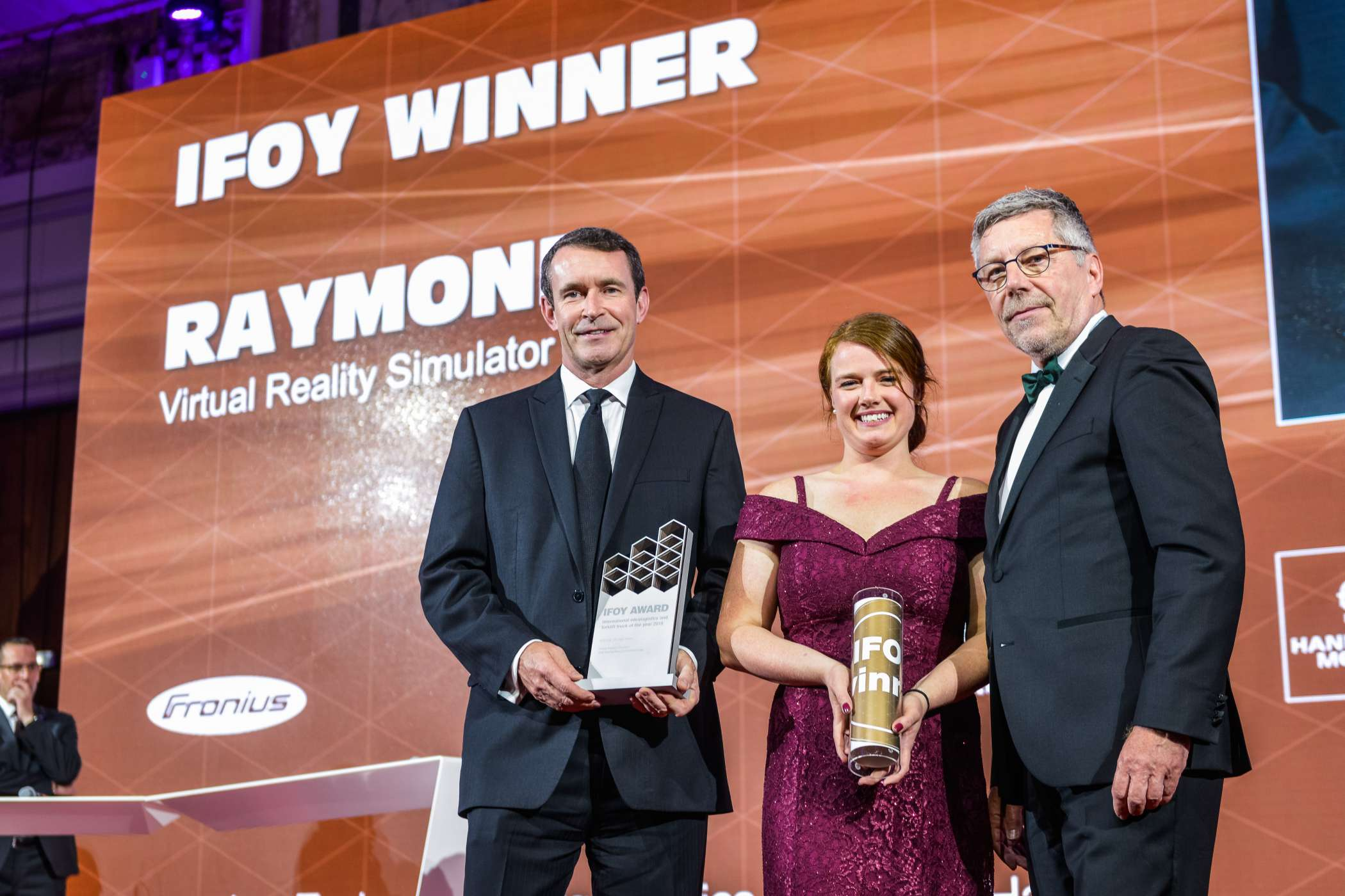 "Kategorie Special of the Year: Die US-Amerikaner von The Raymond Corporation erhalten den IFOY AWARD 2019 für den ""Raymond Virtual Reality Simulator"". Raymond-CEO Michael Field (li.) und Stacey Patch (Raymond Business Manager Virtual Reality Simulator) erhalten die Trophäe aus den Händen von Christian Labrot, Präsident der International Road Transport Union (IRU). (Foto: Oskar Streimel/IFOY)"